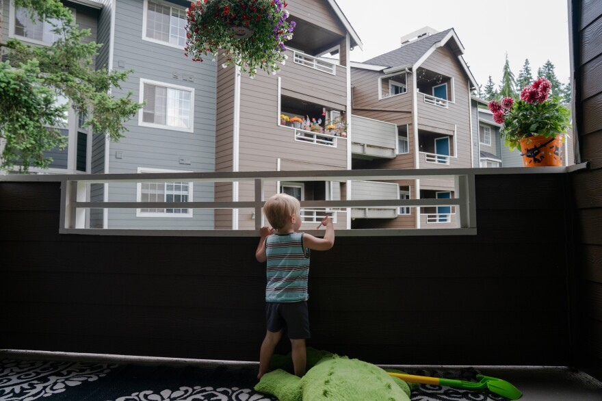"""Grigory Vodolazov's 3-year-old son peers into his family's apartment complex from their unit in Bellevue, Wash. The Vodolazov family is part of Creating Moves to Opportunity, a housing voucher experiment that uses incentives and counseling to encourage low-income families to move to what are called """"high opportunity"""" areas."""