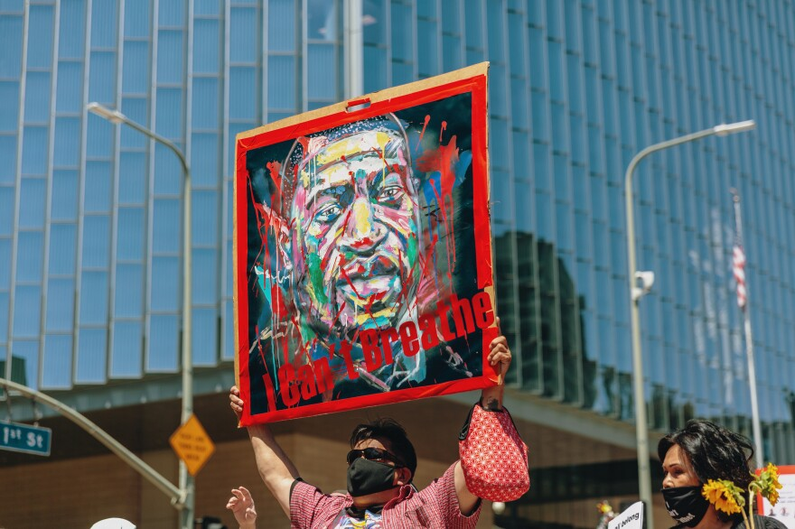 A protester holds a sign with George Floyd's face during a march Monday in Los Angeles to honor black lives lost to police brutality.