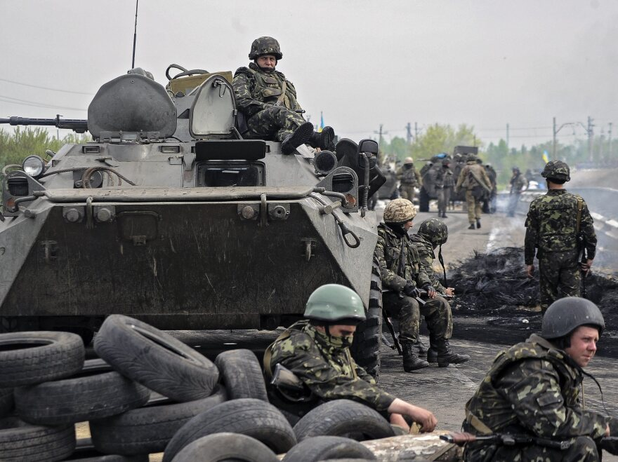 """Ukrainian soldiers stay near a checkpoint they seized not far from Slovyansk, Ukraine, on Friday. Ukrainian officials say two helicopters were shot down during an """"anti-terror"""" operation against pro-Russia separatists."""