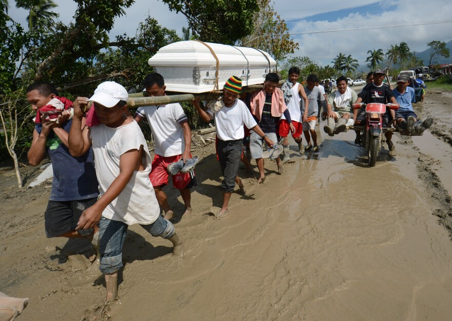 Residents carry a relative's coffin along a muddy road in the town of New Bataan, compostela province on Thursday. Nearly 200,000 people are homeless and more than 300 dead after the Philippines suffered its worst typhoon this year.