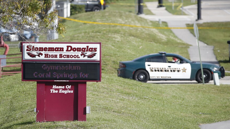 Law enforcement officers block off the entrance to Marjory Stoneman Douglas High School on Feb. 15 in Parkland, Fla. A day earlier a gunman opened fire in the school, killing 17 people.