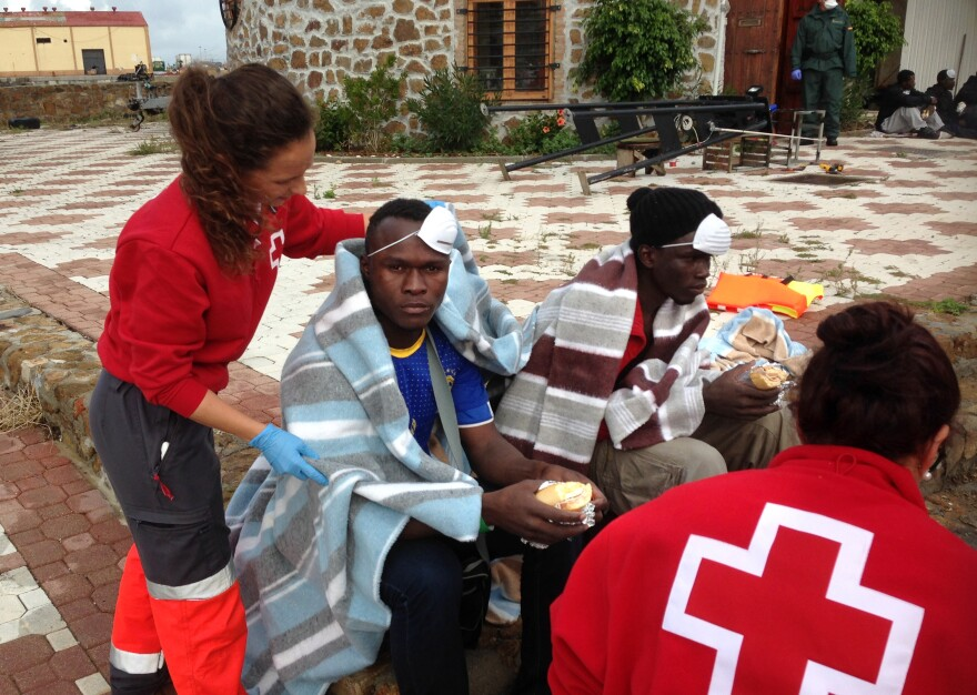 Red Cross medics treat African migrants on arrival in Ceuta. Many travel across the Mediterranean Sea by inflatable raft or by swimming from Morocco. Others scale the fence or cross the border hidden in trucks or cars.