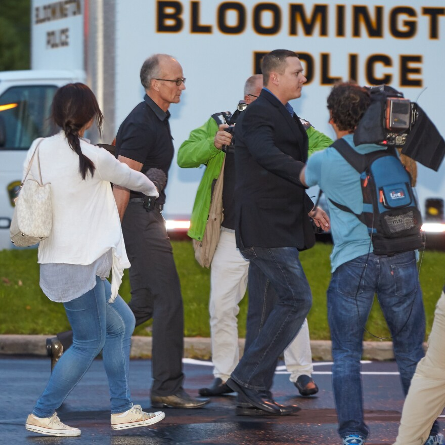 Dentist Walter Palmer (left, in short sleeves) walks into his clinic with private security and members of the media last month in Bloomington, Minn. Protests over his killing of a lion in Zimbabwe had forced him to temporarily close his practice. Now officials say they will not prosecute him.
