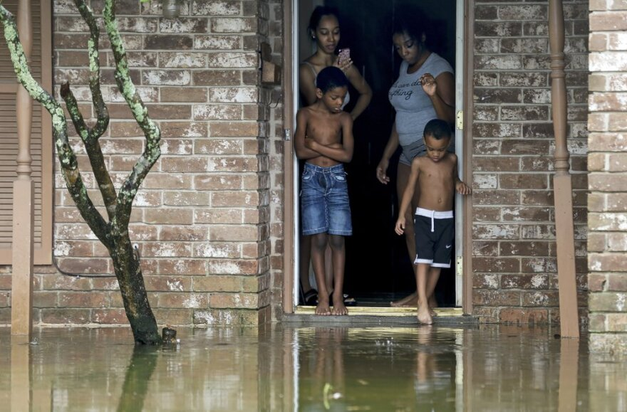 Two young boys and two adult women stand in the doorway of their home, observing their flooded front lawn. The water reaches to the bottom of their doorway.
