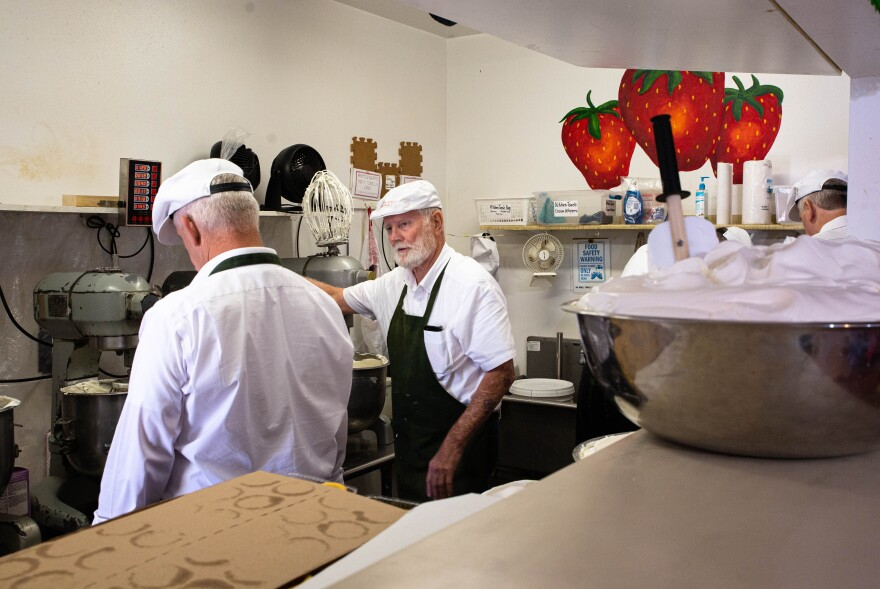 Men in hats and aprons stand in a kitchen preparing baked goods.