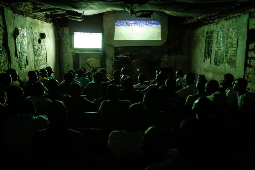 Young men, and the occasional woman, squeeze into Justina's video club in Ganta to watch soccer.
