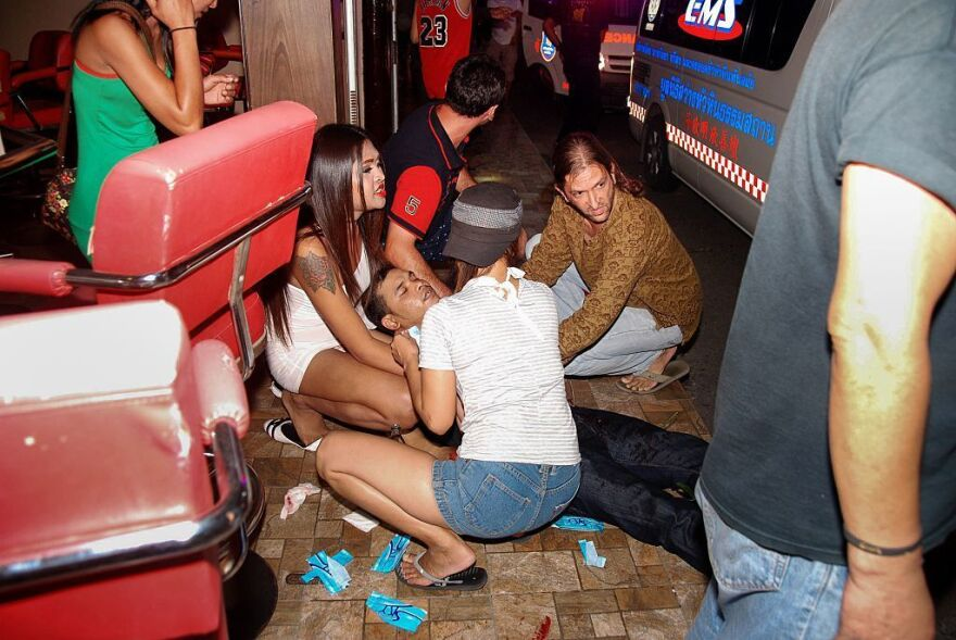 People help an injured man after twin bombs exploded in the upscale resort of Hua Hin, Thailand, on Thursday.