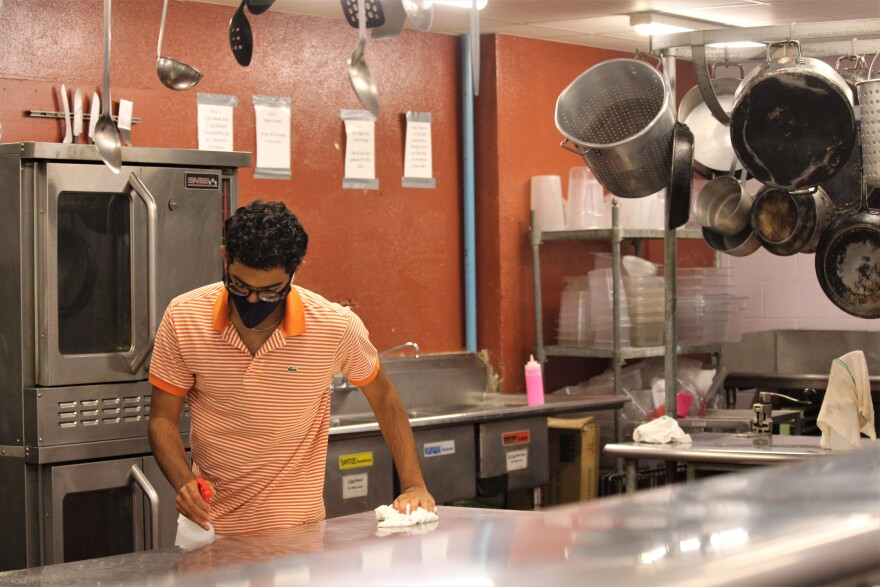 A Taos co-op resident wraps up a nightly deep clean in the kitchen in September 2020.
