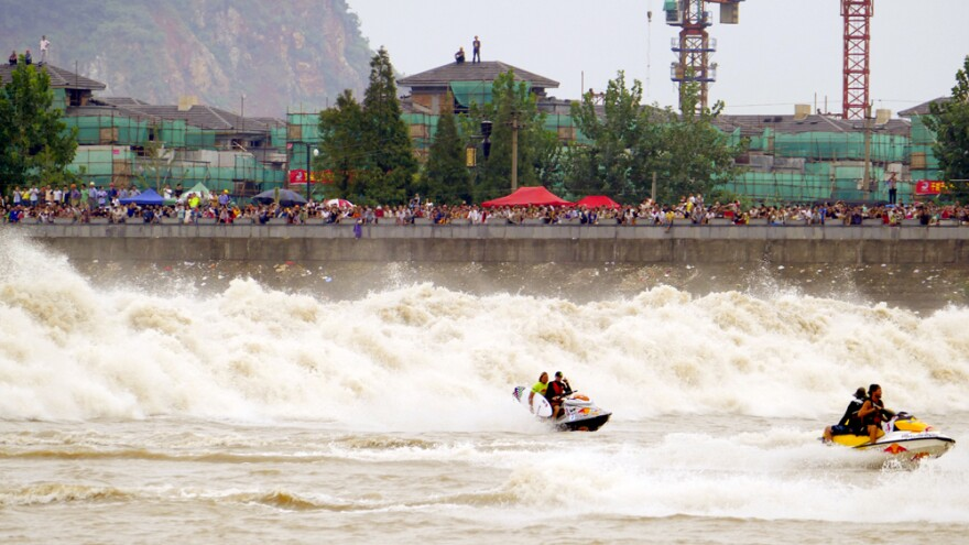 Surfers race in front of the Qiantang Tidal Bore. The wave travels upriver and forms during China's Mid-Autumn Festival, when the moon is full.