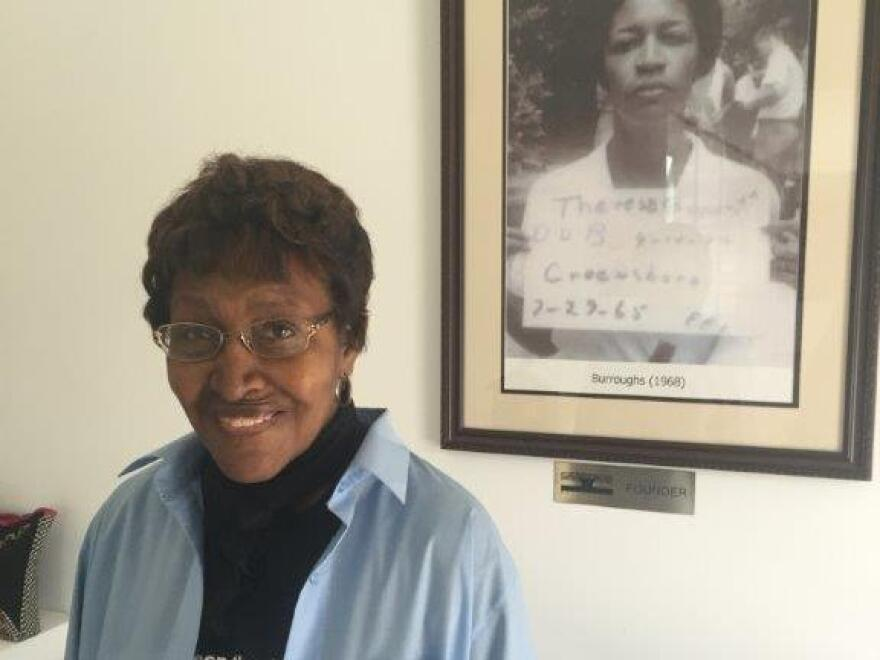 """Civil rights """"foot soldier"""" Theresa Burroughs in 2016, in front of a photo of the day she was arrested in 1965. Burroughs has died at age 89."""