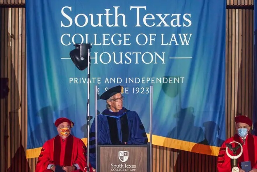 A professor in official robes speaks at a South Texas College of Law commencement ceremony.