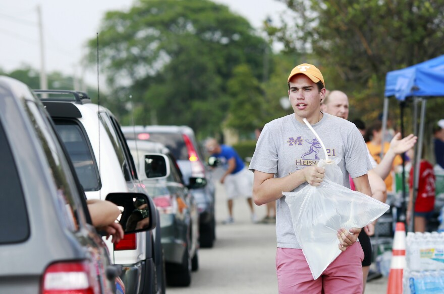 Grant Buehrer, a student at Ohio State University, volunteers to load a 5-pound bag of fresh drinking water into a vehicle on Sunday.