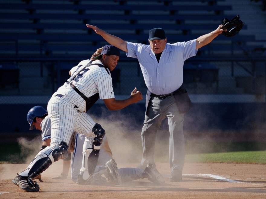 A baseball umpire ruling player 'safe' at home plate.