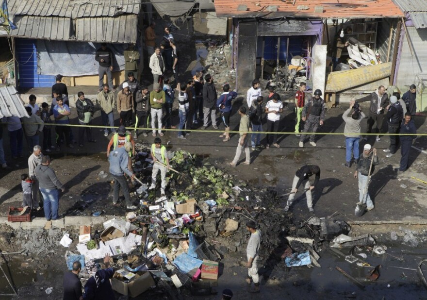 People gather at the scene of a car bomb attack in Zafaraniyah, <a></a>Baghdad, Iraq on Friday. A suicide bomber detonated an explosives-packed car near a funeral procession killing and injuring dozens of Iraqis, police said.