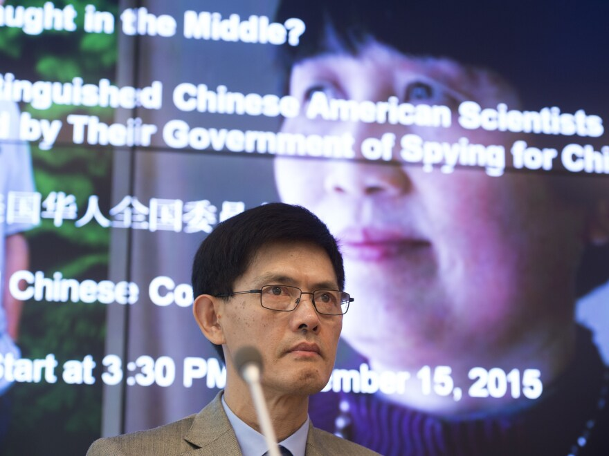 Xiaoxing Xi, a Temple University physics professor, speaks in front of a photo of Sherry Chen, a federal government worker, at a September 2015 Washington, D.C., press conference about the spying charges against them that were dropped. Xi says his wife and daughters were marched out of their bedrooms at gunpoint when he was arrested in May 2015.
