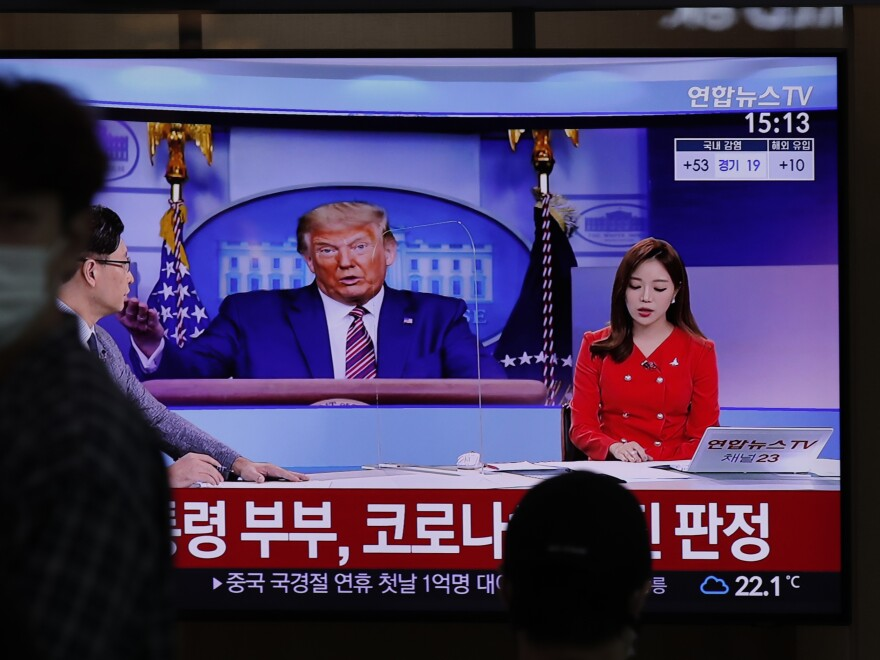 "People pass a TV screen on Friday at the Seoul Railway Station. The Korean words on the screen say, ""President Donald Trump and First Lady Melania Trump tested positive for COVID-19."" South Korean President Moon Jae-in sent Trump a message offering ""solace and encouragement."""