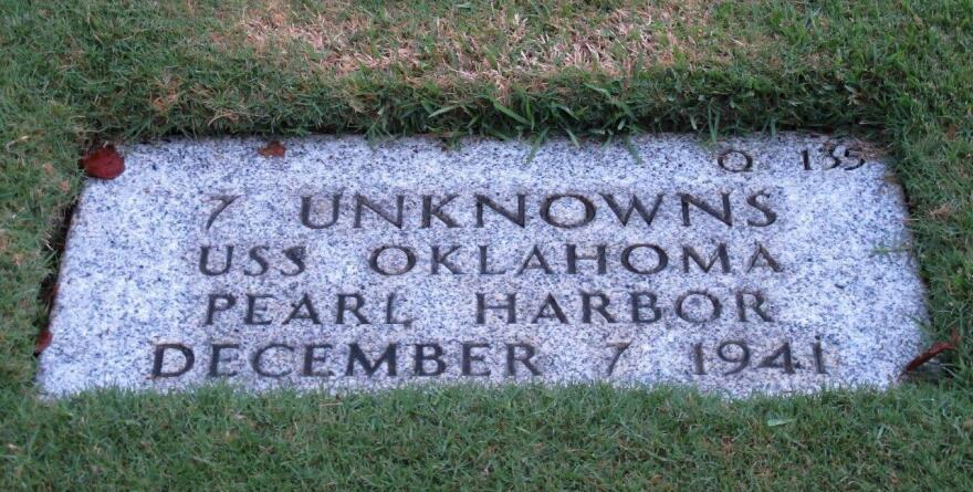 A gravestone identifying the resting place of seven unknowns from the USS Oklahoma is shown at the National Memorial Cemetery of the Pacific in Honolulu. The Pentagon says it will disinter and try to identify the remains of up to 388 unaccounted for sailors and Marines killed when the ship capsized in the 1941 Japanese bombing of Pearl Harbor.