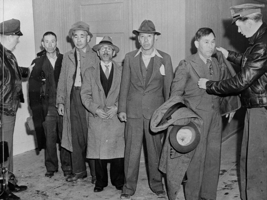 American policemen gather Japanese Americans to transport them to incarceration camps.