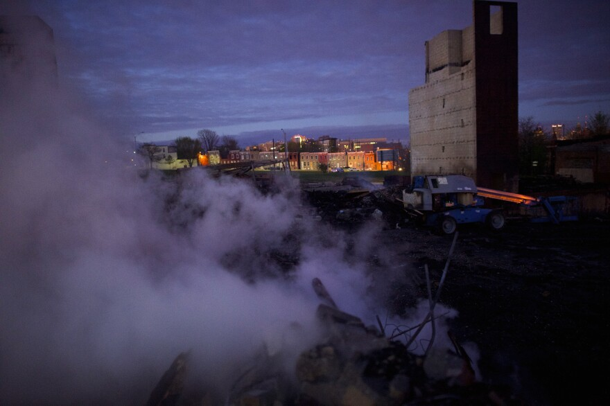 The charred remains of a newly constructed senior center in east Baltimore smolder at dawn on Tuesday.