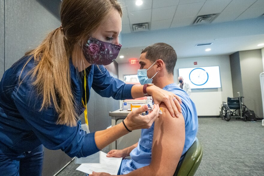 a woman gives a health care worker a vaccine
