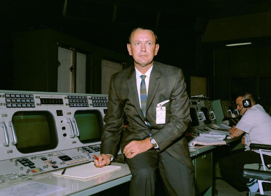 Kraft is seen at his flight director console in the Mission Control Center.