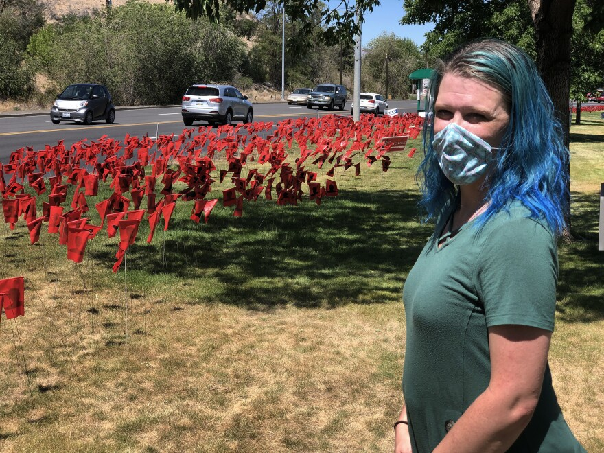 Leola Reeves has set up more than 8,000 red flags, each one with a black silhouette, to represent COVID-19 cases in Yakima County, Wash.