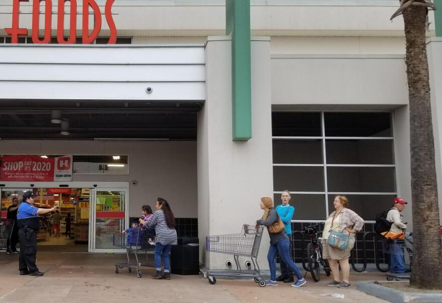 An H-E-B employee lets shoppers into the store as others leave.