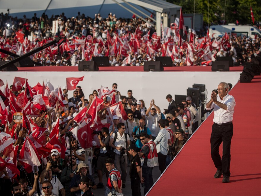 Opposition leader Kemal Kilicdaroglu throws flowers to supporters on Sunday during a massive rally in Istanbul concluding a 280-mile march from Ankara.