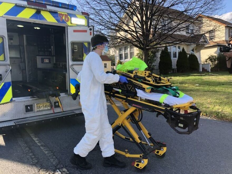 Teaneck Volunteer Ambulance Corps member Bobby Alexiou, 20, wheels out a stretcher outside the home of a potential COVID-19-positive patient in Teaneck, N.J., after suiting up in a protective suit, donated goggles from the local high school and an N95 mask.