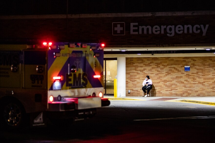 A person wearing a mask waits outside St. David's Medical Center in Austin.