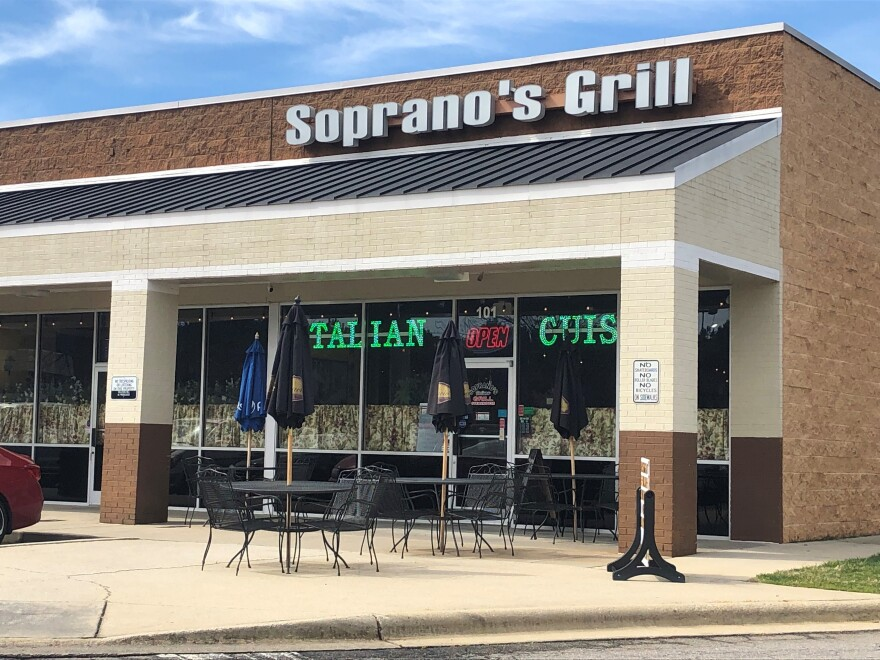 A man shot and wounded by a Raleigh Police officer on Tuesday, was seen by a 911 caller outside Soprano's Grill, allegedly flashing a gun.