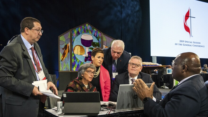 Leaders from the United Methodist Church confer during the 2019 Special Session of the General Conference of The United Methodist Church in St. Louis, Mo. America's second-largest Protestant denomination faces a likely fracture as delegates voted to strengthen bans on same-sex marriage and ordination of LGBT clergy.
