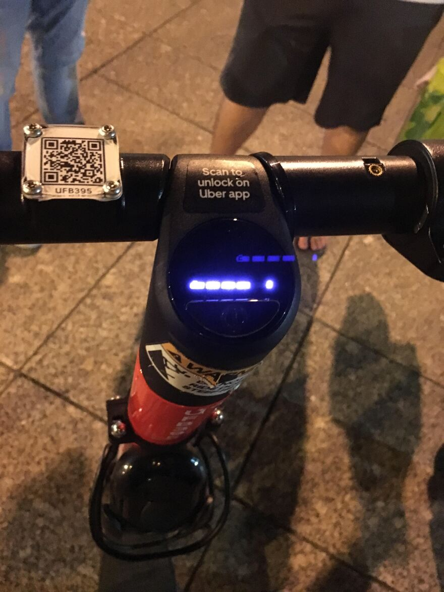 A tiny QR code is bolted to the handlebars of an e-scooter.