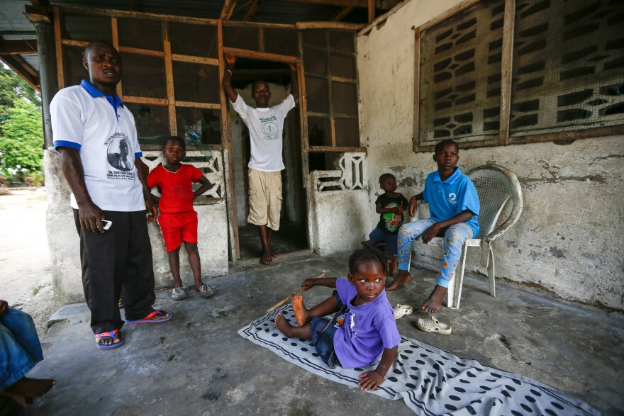 Tarwo Kah, assistant pastor of Christ Kingdom Harvest Church, stands on the porch of the apartment that his church found for the Kaifa family, who lost their parents to Ebola. The boy in the doorway is Morris Kaifa, 15, and the others include (from left) Benetta, 4, Antoinette, 2, and Prince, 10.