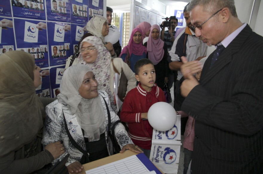 <p>Unidentified supporters of the islamist Ennahda party reacts at the party's headquarters in Tunis on Monday.</p>