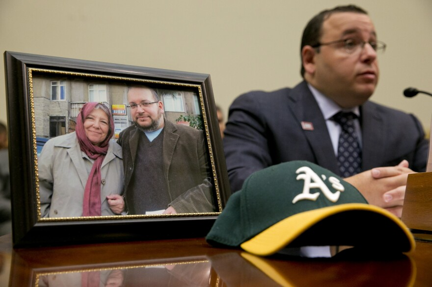 Ali Rezaian, brother of imprisoned <em>Washington Post</em> journalist Jason Rezaian, speaks by a picture of Jason and his mother on June 2. A verdict has been reached in Jason Rezaian's case, an Iranian official says, but it's not clear what the verdict is.