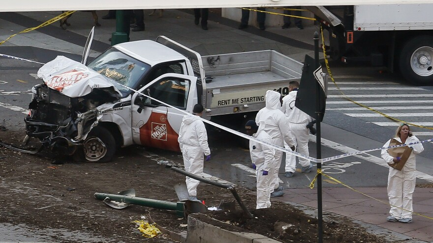 Authorities stand near a damaged truck after an attacker drove onto a bike path in New York City, striking and killing eight people Tuesday. The Islamic State has been calling on supporters to use vehicles to carry out attacks for the past year.