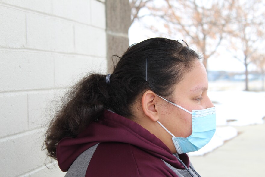 A Hispanic woman looking to the right with a mask on her face.