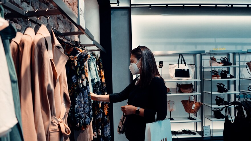 Woman wears a mask as she holds shopping bags and browses clothing racks.