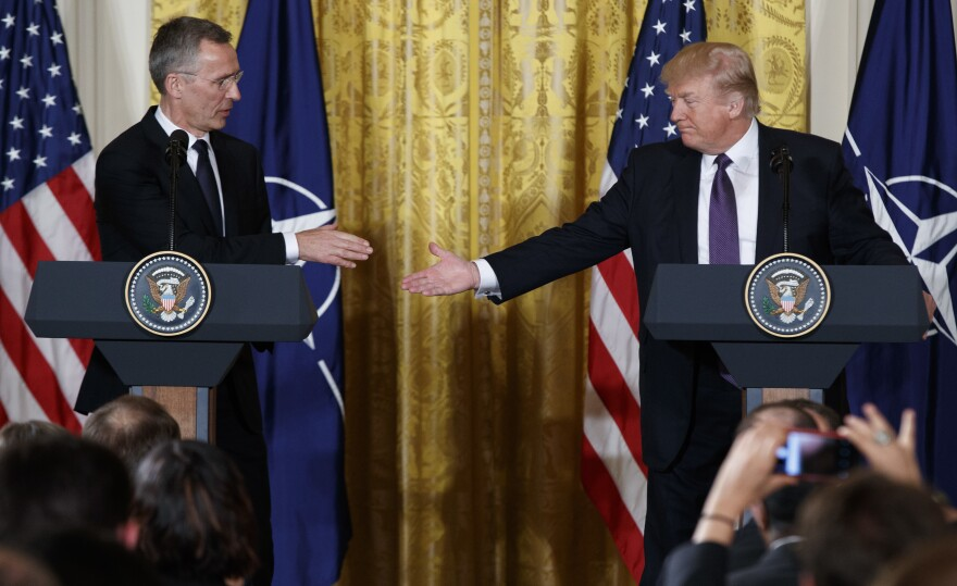 President Trump reaches to shake hands with NATO Secretary General Jens Stoltenberg during a news conference in the East Room of the White House on Wednesday.