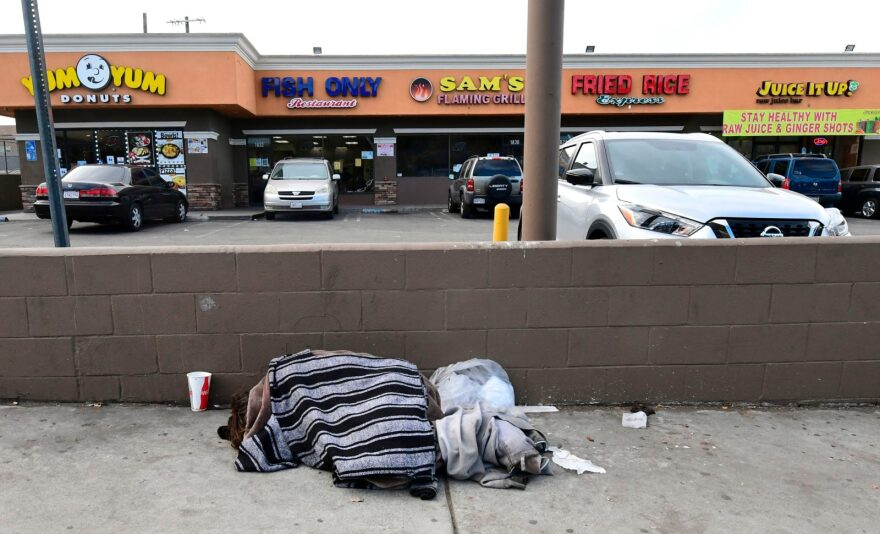 A person experiencing homelessness sleeps on the street as some businesses remain open despite the Stay-At-Home regulations underway in Los Angeles, California.