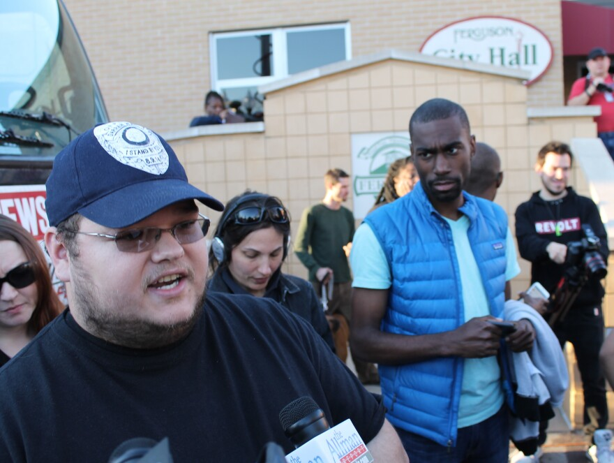 "Florssiant resident Bill Piepers speaks to the media as Deray McKesson looks on. Piepers was wearing an ""I Am Darren Wilson"" hat, which showcased support for the police officer who shot and killed Michael Brown."