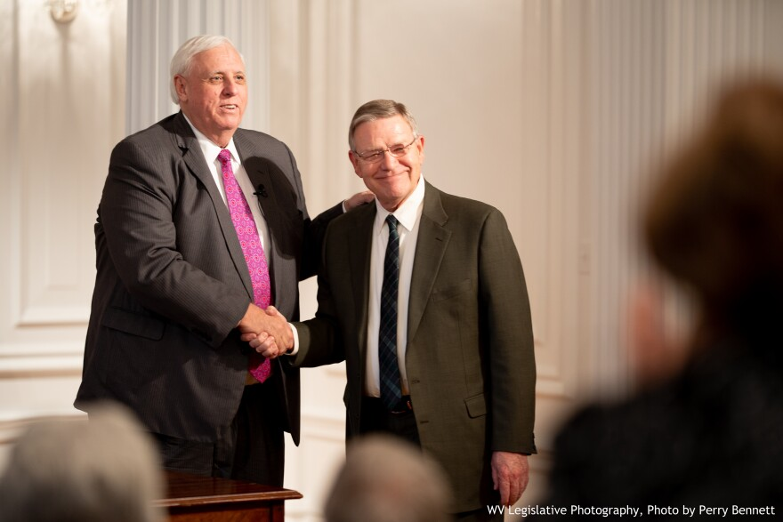 Outgoing W.Va. Senator Ed Gaunch, R-Kanawha (right), shakes hands with Gov. Jim Justice on Dec. 4, 2018 as he accepts the position of Secretary of Commerce.