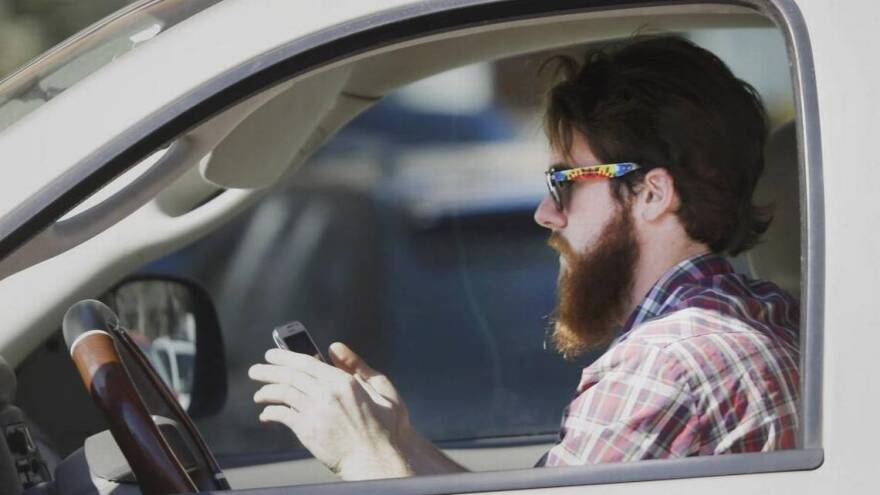 A man is distracted by his cell phone while driving through traffic.