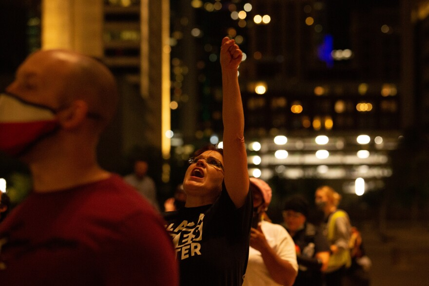 Photo of Deborah Spanier standing in a crowd wearing a Black Lives Matter t-shirt shouting with her fist in the air.