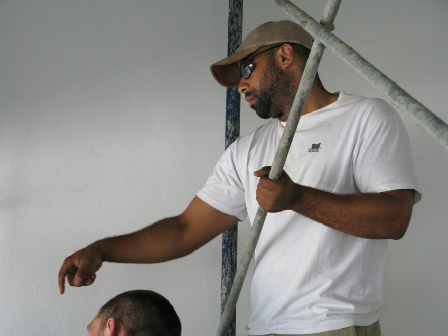 """Dr. David Walton, a physician from Boston, oversees the final touches on the staircase of the main lobby of the National Teaching Hospital in Mirebalais, Haiti. """"One of the lessons this hospital can provide is how to provide really outstanding infrastructure and construction practices at a fraction of what it may cost in other settings,"""" he says."""