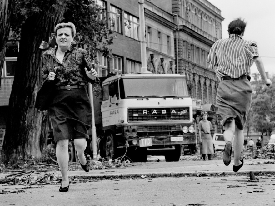 """In this photo from 1992, women run across """"Sniper Alley"""" under the sights of Serb gunmen during the siege of Sarajevo."""