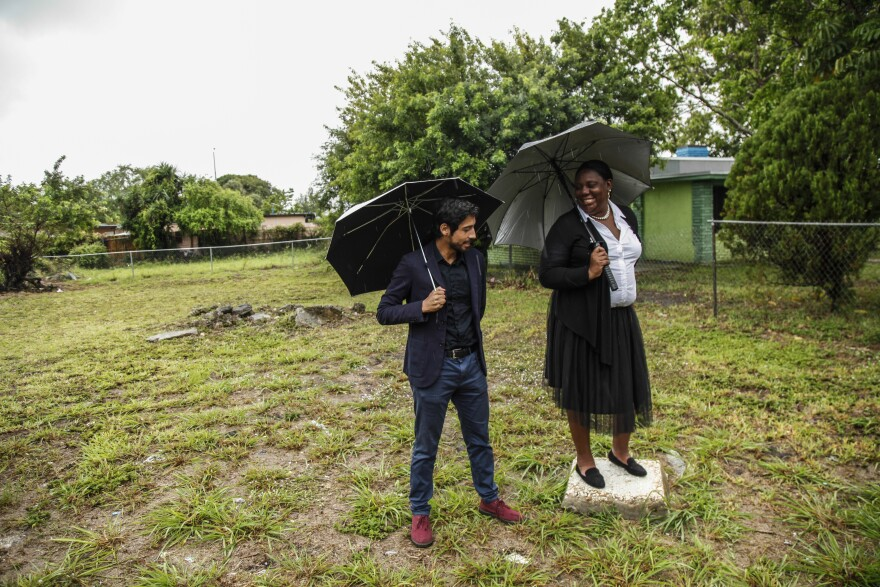 "Adrian Madriz (left) with Trenise Bryant at the site of their planned community land trust and apartment building in Miami's Liberty City neighborhood. They say the project will provide housing for low-income locals and help resist so-called ""climate gentrification."""