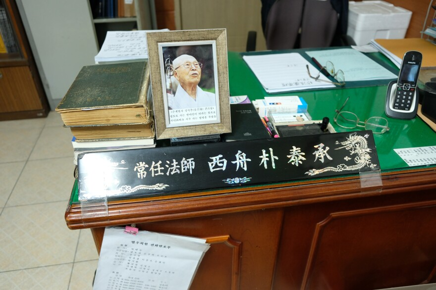 "On the desk in Park's office sit a picture of his Buddhist master and a sign showing the Buddhist name the master gave him, written in Chinese, which translates to ""Ship to the West."" The name refers to Park's mission to help the souls of fallen child soldiers."
