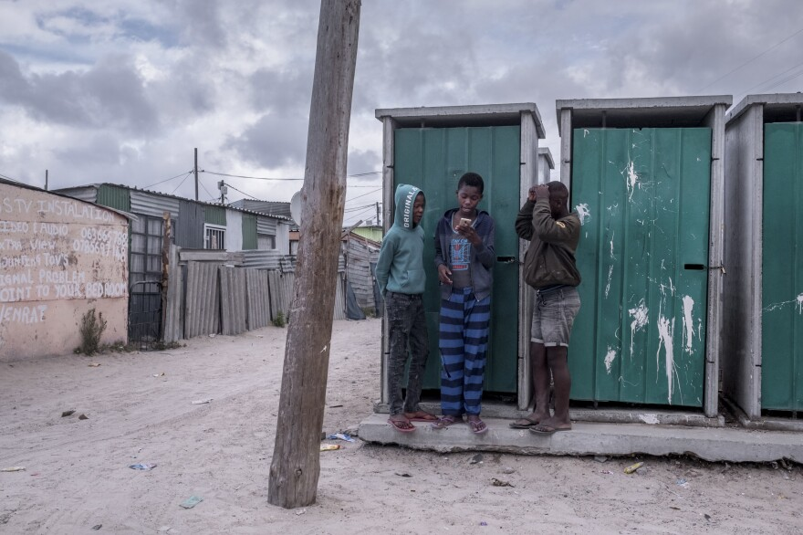 Boys gather at the communal toilets to get a cellphone signal in the township of Khayelitsha, Cape Town.